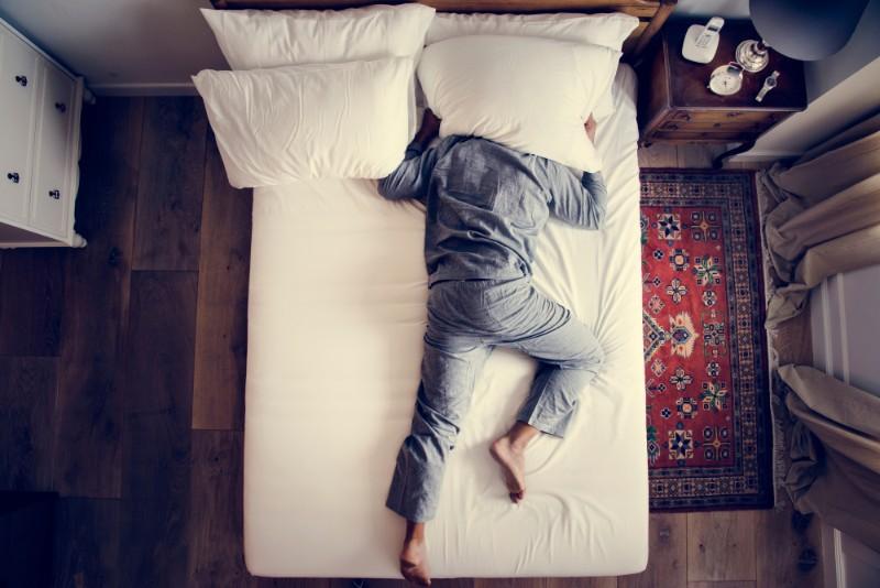 ベッドで寝転がりながら枕で頭を覆う男性