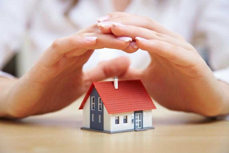 家の模型を覆っている手