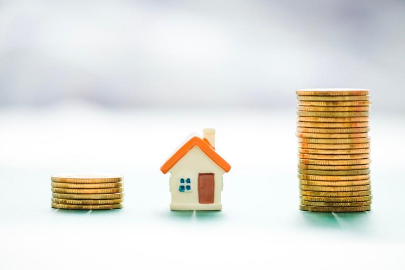 家の模型と積まれたコイン